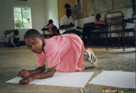 African child on floor in classroom